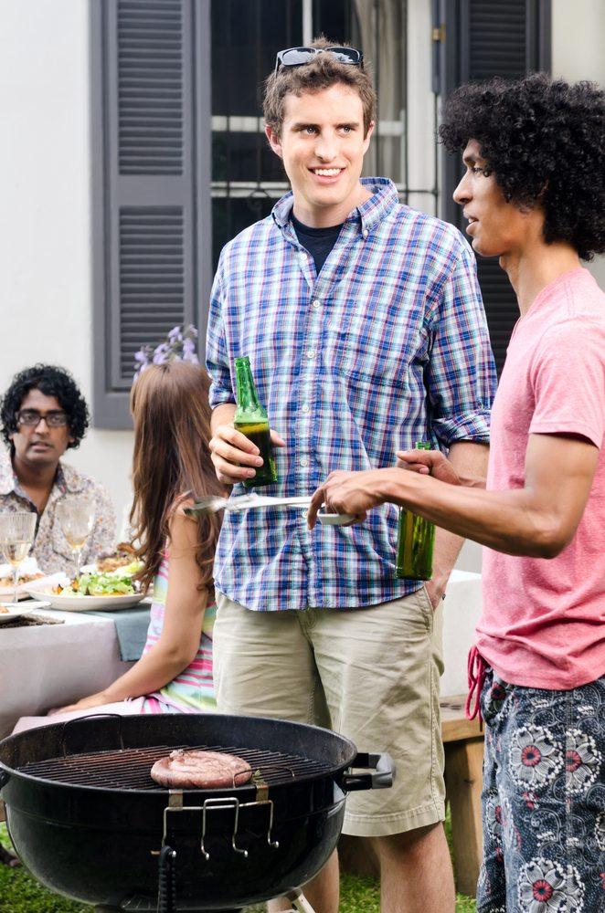 Men standing around a bbq drinking beer