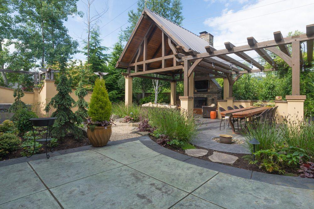 An upscale backyard terrace featuring perennials, a shelter, and a fireplace