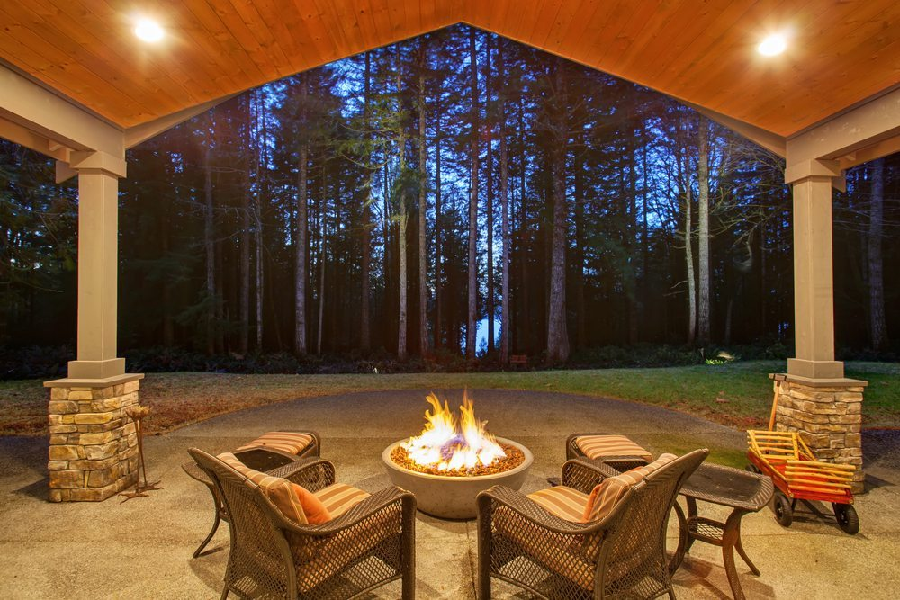 large backyard with grass and patio heaters and fire pit